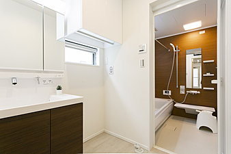 石鹸・シャンプー、洗剤などのストックは洗濯機上部の収納へ。歯ブラシ、化粧品、髪留めなどのこまごましたものはミラー裏へ らくらく収納。浴室には追い炊き機能、暖房・乾燥機搭載。(同シリーズ内観イメージ)