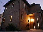 夕暮れ時の外観です。窓からこぼれる明かりと、ベージュのタイル外壁が優しい陰影をつくります。
