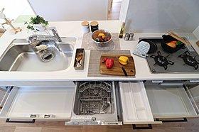 重厚なカウンターと大型収納を設けたキッチンダイニング