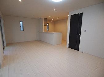 開放的なI型対面キッチンと、白い床材の清潔感がマッチしたLDKです。扉を黒にすることにより、空間に締まりとアクセントを施してくれています。