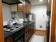 オーブンなどもある設備充実のキッチンのようすです。食器棚は造り付けになっています。