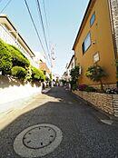 静かな街並みが広がる近隣風景。光に満ちた住宅街の通りを澄んだ空気、やわらかな風が吹き抜けていきます。