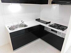 リフォーム後/キッチンL型の3口コンロシステムキッチンを導入致しました。床の白とメリハリをつける為、お洒落な黒系の扉になっております。