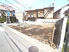 西側の前面道路から現地に向かって撮影しました。前面道路はどちらも6m以上と広いので、より開放感を感じます。(平成30年4月9日撮影)